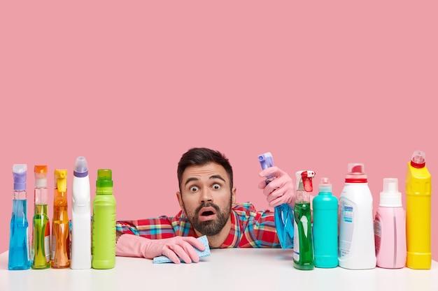 Foto isolada de um homem barbudo com expressão de choque, olha para você, segura o spray e usa pano para limpar