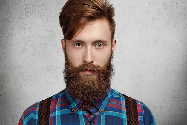 Foto isolada de um homem caucasiano elegante e atraente com barba e bigode difuso, vestindo uma camisa quadriculada, com uma expressão séria e pensativa enquanto pensa em algo