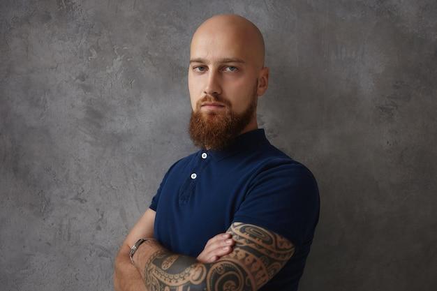 Foto isolada de um homem jovem sério elegante com a cabeça raspada, tatuagem de barba ruiva difusa cruzando os braços sobre o peito, vestindo uma camisa pólo da moda,