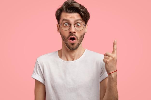Foto isolada de um homem surpreso com a barba por fazer engasga de espanto, aponta com o dedo da frente para cima, usa óculos redondos e camiseta branca, modelos contra uma parede rosa, demonstra algo acima