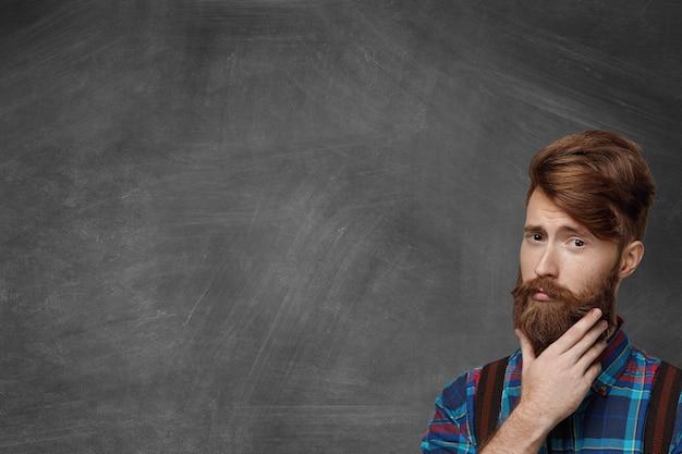 Foto isolada de um jovem bonito com um corte de cabelo estiloso, vestido com uma camisa xadrez e suspensórios, gerando novas ideias, tocando sua barba espessa com um olhar pensativo, tentando se lembrar de algo
