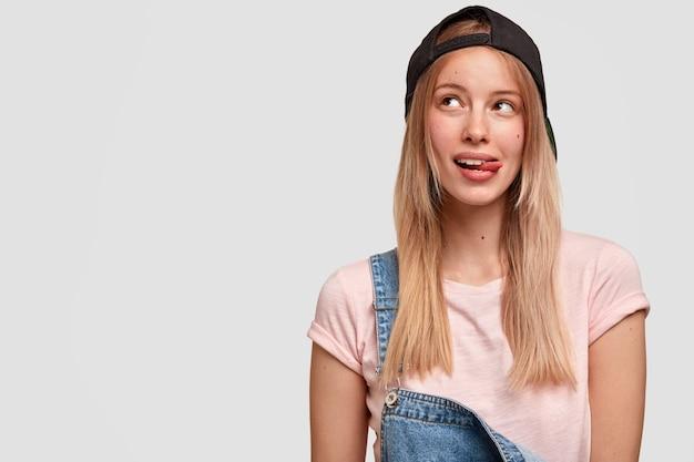 Foto isolada de uma adolescente bonita na moda olha de lado com uma expressão sonhadora, mostra a língua, usa boné e macacão pretos da moda, contempla algo agradável, fica em pé