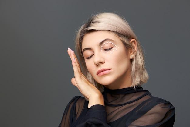 Foto isolada de uma adorável jovem de 20 anos com uma blusa preta transparente, mantendo os olhos fechados e tocando suavemente sua pele macia usando um piercing no nariz, corte de cabelo estiloso e maquiagem brilhante