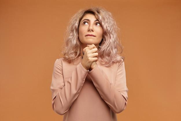 Foto isolada de uma bela jovem europeia elegante com piercing no nariz e cabelo rosado, de mãos dadas e olhando para cima com expressão facial triste e esperançosa, rezando