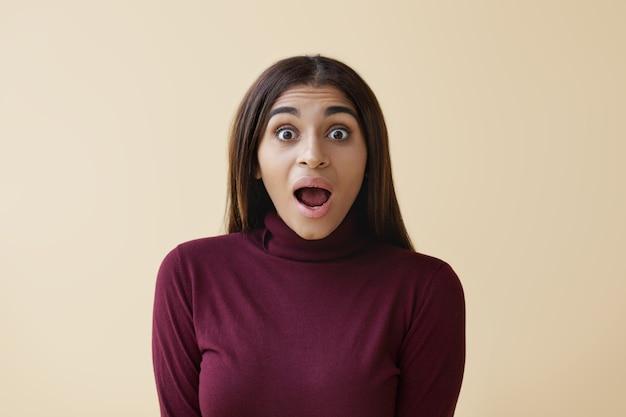 Foto isolada de uma bela mulher afro-americana com cabelo liso solto abrindo a boca amplamente, perdendo-se nas palavras, tendo um olhar surpreso, chocada com preços de venda altos ou informações surpreendentes