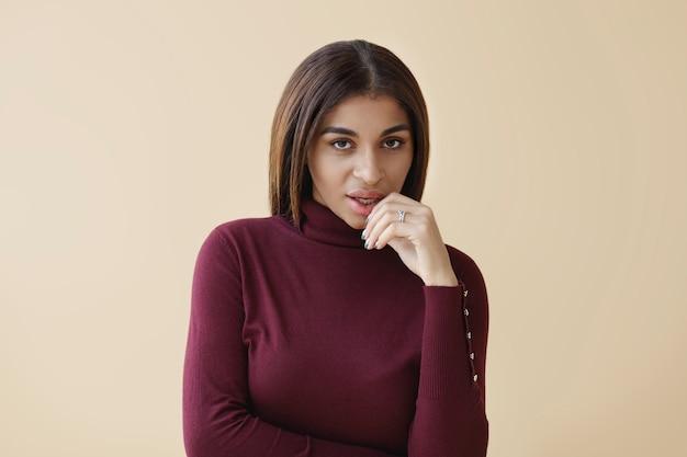 Foto isolada de uma elegante jovem morena de pele escura usando um suéter roxo da moda, de gola alta, posando, olhando com um olhar misterioso e brincalhão, tocando seus lábios macios