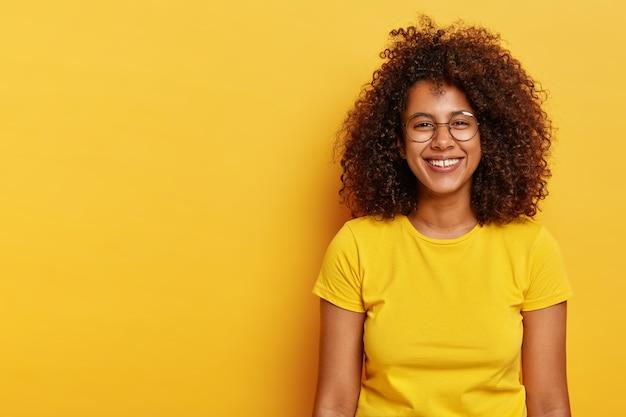 Foto isolada de uma garota afro bonita e feliz com cabelo escuro e espesso, usa óculos grandes e redondos, camiseta amarela brilhante, sorri feliz, feliz por ter um dia de sucesso, modelos dentro de casa, sente-se relaxada e despreocupada
