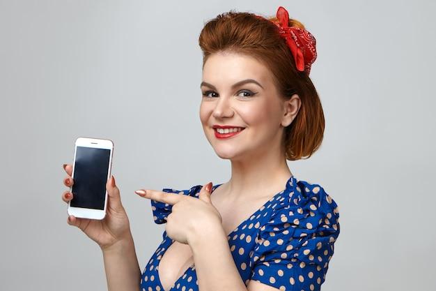Foto isolada de uma jovem e elegante modelo feminina vestindo roupas retrô e batom vermelho, sorrindo alegremente, promovendo um aparelho eletrônico moderno, segurando um celular genérico