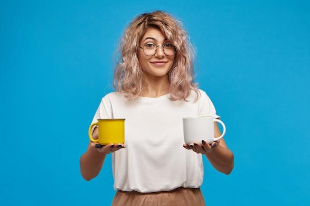 Foto isolada de uma jovem europeia elegante e charmosa com óculos redondos elegantes e uma camiseta enorme, com aparência amigável, segurando duas xícaras de bebidas quentes