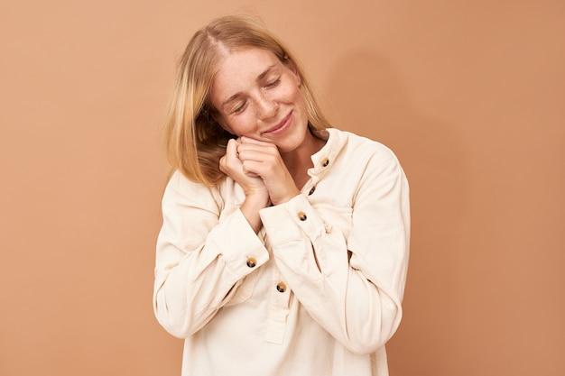 Foto isolada de uma jovem europeia fofa satisfeita colocando o rosto nas mãos, tirando uma soneca, sorrindo gentilmente, tendo sonhos agradáveis à noite