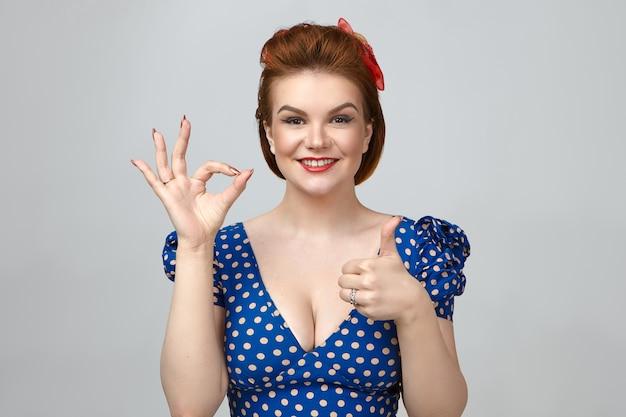 Foto isolada de uma jovem linda e encantadora usando um vestido vintage pontilhado com decote baixo e de bom humor.