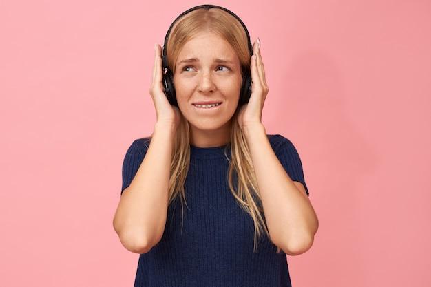 Foto isolada de uma linda adolescente de mãos dadas nos ouvidos, curtindo faixas de música de alta qualidade no mp3 player usando fone de ouvido sem fio