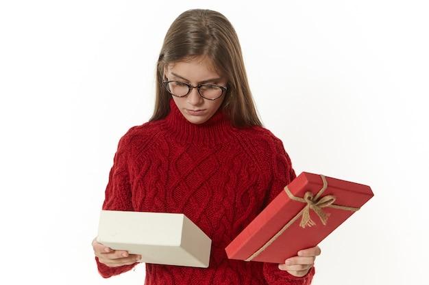 Foto isolada de uma linda jovem com óculos elegantes e pulôver marrom segurando uma caixa aberta com um presente de aniversário, com uma expressão facial triste e desapontada, não gosta do que está dentro