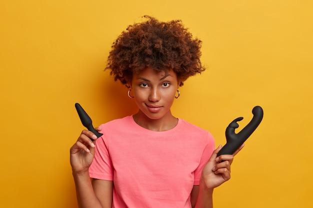 Foto isolada de uma mulher afro-americana posando com brinquedos sexuais, usa plug anal para sexo anal e vibrador de coelho para liberar a tensão sexual e melhorar seu humor, aumenta a função sexual e obtém prazer pessoal