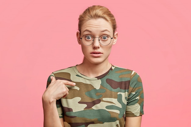 Foto isolada de uma mulher atraente atordoada indica uma camiseta nova, sendo surpreendida com o alto preço das roupas no shopping, posa contra o estúdio rosa