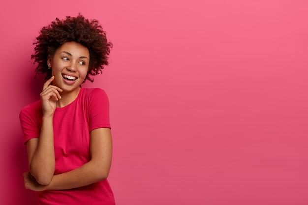 Foto isolada de uma mulher bonita com cabelo encaracolado natural, olha para o lado e tem pele escura, toca o rosto, sorri com os dentes, veste uma camiseta casual, posa contra a parede rosa, espaço em branco para seu anúncio