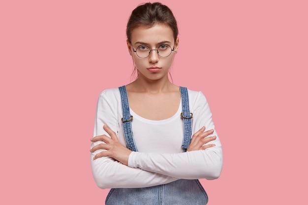 Foto isolada de uma mulher caucasiana séria com olhar zangado e de braços cruzados