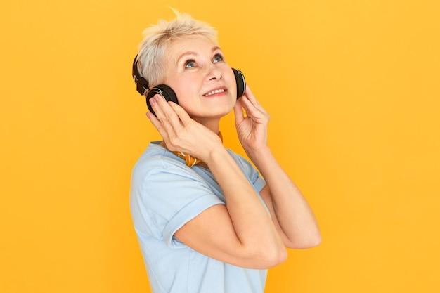 Foto isolada de uma mulher europeia de meia-idade encantadora, pensativa, usando um fone de ouvido sem fio, ouvindo faixas de música clássica e desfrutando de som mp3 de alta qualidade, olhando para cima com uma expressão facial sonhadora