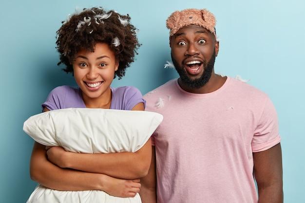 Foto isolada de uma mulher feliz de pele escura e um homem com expressões de alegria, recebe uma surpresa magnífica pela manhã, tem penas no cabelo, fica perto um do outro, isolado na parede azul