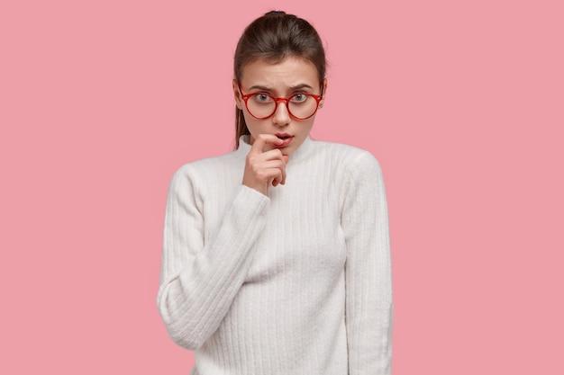 Foto isolada de uma mulher séria de aparência agradável mantendo o dedo da frente perto dos lábios, olhando seriamente através dos óculos, vestida com roupas casuais brancas