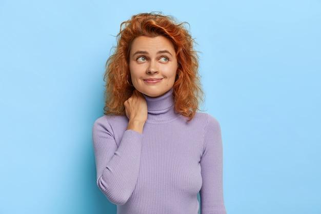 Foto isolada de uma mulher sonhadora de cabelos cacheados ruivos com um olhar pensativo satisfeito, concentrada à parte, usa um macacão de gola pólo roxo, lembra do primeiro encontro com o namorado, isolada sobre uma parede azul
