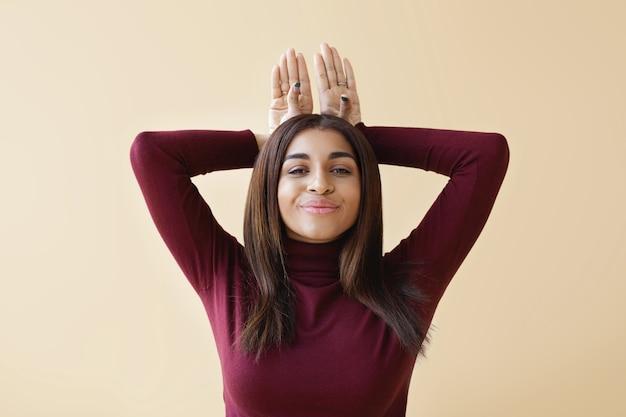 Foto isolada horizontal de uma mulher jovem e atraente de raça mista com roupas elegantes, sorrindo alegremente e mantendo as mãos atrás da cabeça, imitando o coelho enquanto se diverte