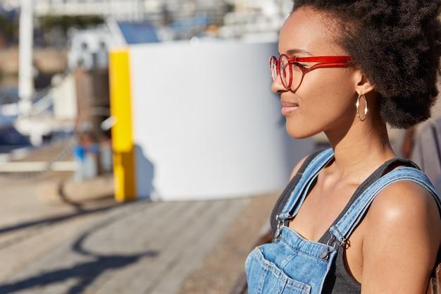 Foto lateral ao ar livre de uma jovem negra satisfeita com penteado afro, usa óculos, macacão jeans, focada na distância, caminha ao ar livre durante as férias de verão, passeia em cidade desconhecida
