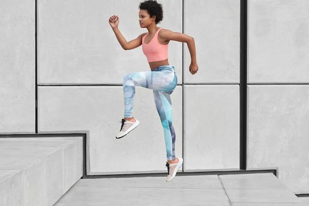 Foto lateral de mulher atlética olha para frente, sobe as escadas correndo, quer perder peso, dá salto em altura, usa roupa esporte, supera o desafio, fotografada em movimento, queima gordura corporal. exercício