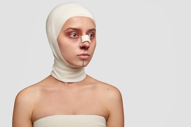Foto lateral de paciente pensativo com curativo médico no nariz, sendo operado por esteticista