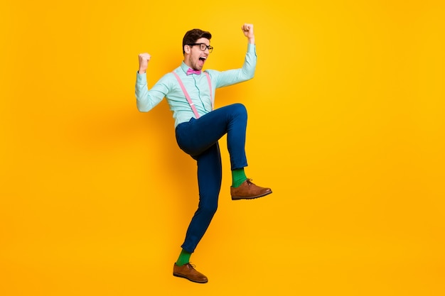 Foto lateral de perfil de comprimento total homem positivo desfrute, alegre-se, ganhe corona vírus covid29 infecção levante os punhos grite sim, use gravata borboleta rosa azul rosa isolado brilhante cor de fundo