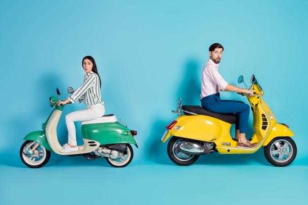 Foto lateral de perfil de corpo inteiro de duas pessoas chocadas homem mulher andando de moto impressionado com grito de alta velocidade wow omg usar camisa calça branca calça isolada sobre parede de cor azul