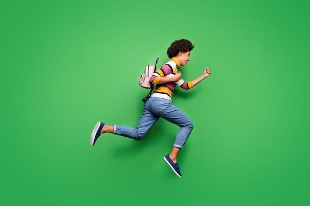 Foto lateral de perfil de corpo inteiro de uma garota afro-americana louca e descolada, pule, corra rápido, queira viajar, outono, jornada, use roupa de mochila brilhante brilho
