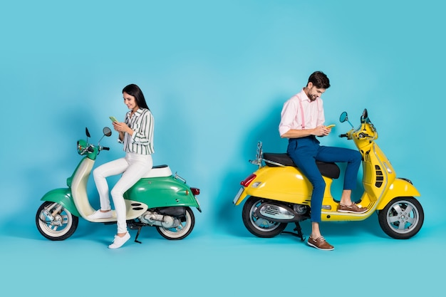 Foto lateral de perfil de corpo inteiro positivo duas pessoas esposa marido piloto sentar moto usar celular navegar caminho caminho destino desfrutar aventura de rua parede de cor azul isolada