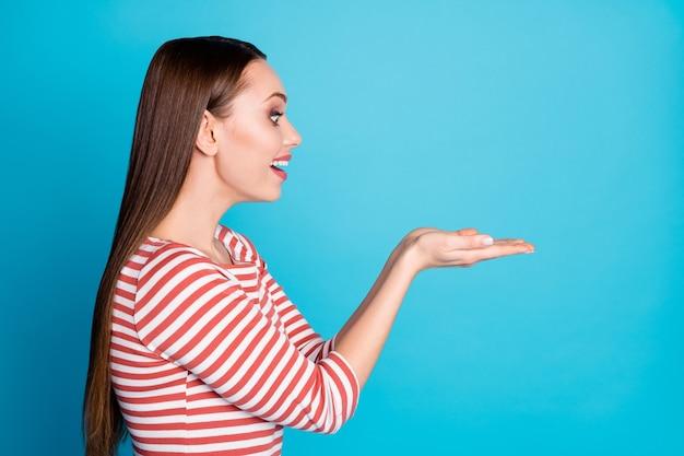 Foto lateral de perfil de menina alegre, surpresa, positiva, segurando a mão, boa aparência, anúncios de promoção incríveis usam roupas de estilo casual isoladas sobre fundo de cor azul