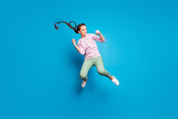 Foto lateral de perfil em tamanho real de garota jovem séria lutando, batalha, salto, chute, pernas, punhos, inimigo, quer ganhar, vestir pulôver rosa, tênis branco jovem isolado sobre o fundo de cor azul