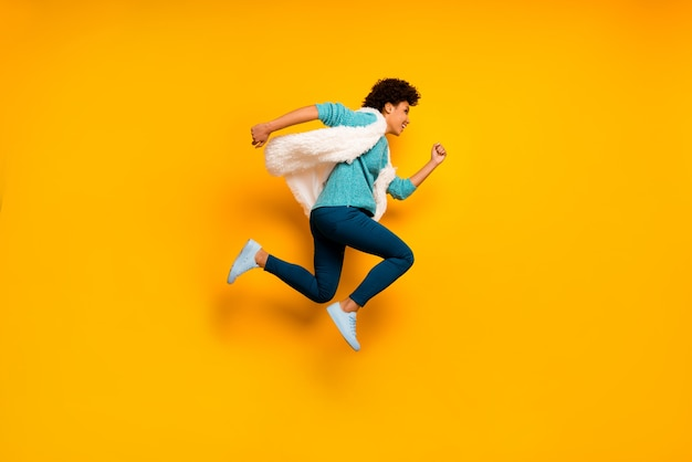 Foto lateral de perfil em tamanho real louca linda garota afro-americana pule, corra, descontos use pressa, use suéter azul-petróleo elegante na moda calça azul branco calça tênis isolado parede cor amarela