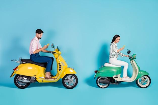 Foto lateral de perfil em tamanho real positivo duas pessoas esposa marido motorista usar celular navegar na internet destino viagem viagem dirigir moto parede azul isolada