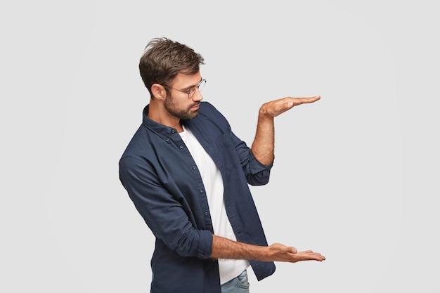 Foto lateral de um homem autoconfiante demonstra o tamanho ou a altura de algo, levanta as palmas das mãos no ar
