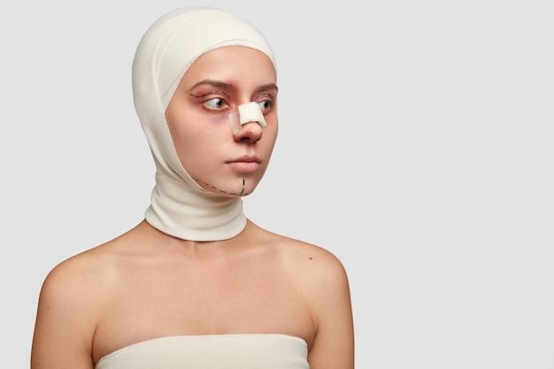 Foto lateral de um paciente pensativo sendo envolvido por uma bandagem após uma operação difícil e dolorosa, nariz arrebitado, sérios danos