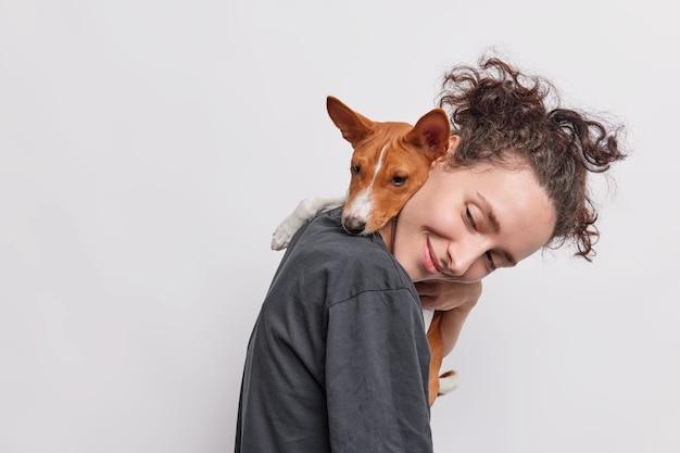 Foto lateral de uma garota adulta carregando um cachorro que a abraça em volta do pescoço caminhando juntos isolados sobre o branco