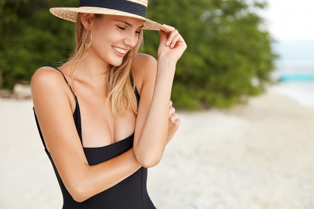 Foto lateral de uma jovem com roupas de verão aprecia uma vista pitoresca e oceanos em uma cidade turística, caminha sozinha na praia, tem um sorriso caloroso e agradável, feliz por receber elogios de estranhos
