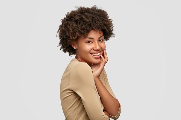 Foto lateral de uma jovem modelo alegre de pele escura com corte de cabelo afro