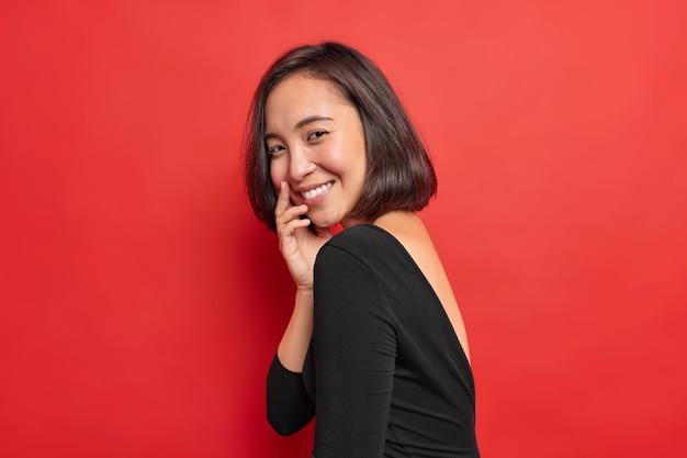 Foto lateral de uma linda mulher asiática sorrindo gentilmente com uma expressão tímida e feliz usando um vestido preto que expressa emoções autênticas e positivas isoladas sobre uma parede vermelha vívida