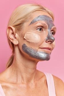 Foto lateral de uma mulher europeia séria com cabelo louro penteado submetida a procedimentos cosméticos para rejuvenescer e nutrir a pele aplica máscara prateada focada em poses distantes contra parede rosa