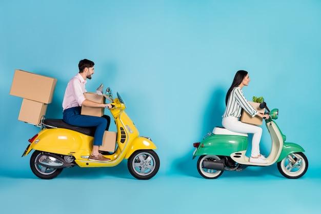 Foto lateral do perfil em tamanho real casal positivo motorista motorista obter hipoteca imóvel mover apartamento moderno dirigir moto carregar pacotes lâmpada flor isolada parede cor azul