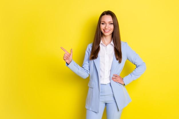 Foto líder positivo chefe tem parceria ponto de encontro dedo indicador copyspace demonstrar anúncios de empresas de negócios usam calças blazer azuis isoladas com fundo de cor brilhante brilhante