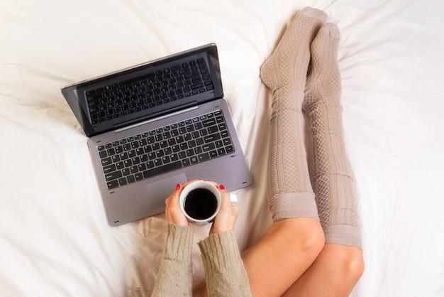 Foto macia da mulher na cama com laptop e xícara de café nas mãos, ponto de vista superior