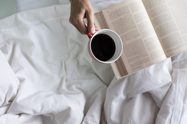 Foto macia da mulher na cama com livro antigo e xícara de café e cópia espaço.