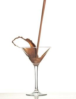 Foto macro com chocolate quente caindo em vidro branco em estúdio