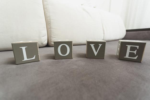 Foto macro da palavra amor escrita por letras em tijolos de madeira